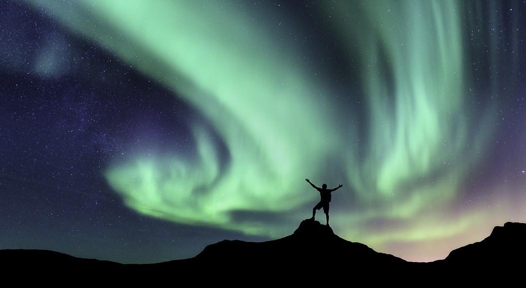 man-op-berg-met-noorderlicht-zweeds-lapland